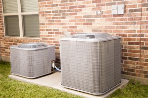 Two air conditioner units outside brick home. Service industry, construction industries.