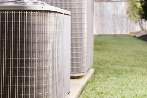 Two air conditioner units outside a large brick home.