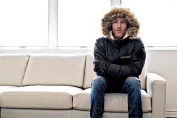 Man wearing winter jacket seating on a sofa