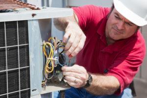 Air conditioning repairman rewiring a compressor unit