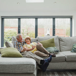 older couple cuddles on their living room couch