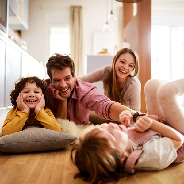 family laughing on their kitchen floor