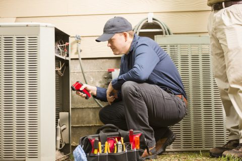 Mid-adult repairman works on a home's air conditioner unit outdoors. Man center is working on the unit using tools in his toolbox. Other man to right. They both wear uniforms.