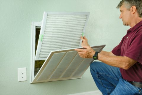 Professional repair service man or diy home owner installing a clean new air filter on a house air conditioner which is an important part of preventive maintenance.